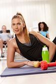 Attractive young girl lying on side at the gym, water, dumbbell and apple front of her.