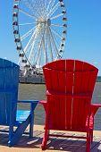 Blue and red chairs on a pier with Ferris wheel on background.