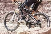 foto of prosthesis  - Shot of mountain bike rider with leg prosthesis between rocks - JPG