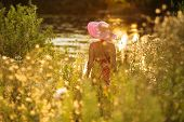 pic of beatitudes  - Woman with hat on the waterfront of meadow flowers - JPG