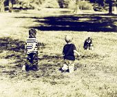 Two Young Boys At A Park Approaching A Dog - Sepia