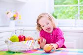 stock photo of day care center  - Funny happy laughing child adorable toddler girl with curly hair wearing a pink shirt eating red and green apples for healthy snack sitting in a white sunny kitchen with window at home or day care center - JPG
