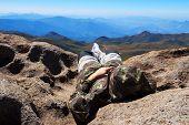 Man Laying On Edge Of Mountain Peak