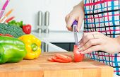Woman Chef Cutting Peppers. Food Preparation In Modern Kitchen
