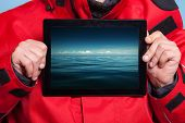 Man Showing Stormy Sea On Tablet. Travel.