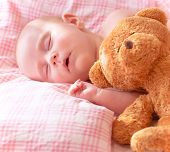 Portrait of adorable newborn baby sleeping on cute pink pillow with soft toy of teddy bear, day drea