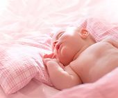 Portrait of cute little sleeping baby, sweet naked newborn girl napping at home, healthy lifestyle,