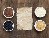 Variety Of Rice In Bowls On Wooden Table And Old Paper