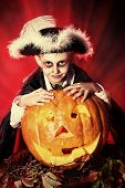 pic of warlock  - Little boy in halloween costume of pirate posing with pumpkins over dark background  - JPG