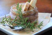 Glass bowl of chocolate mousse with rosemary sprigs