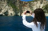 young woman photographs the island in Greece, travel in Zakinthos