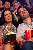 Young couple sitting in movie theater, watching film, having popcorn.