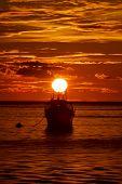 Fishing boats on sea at sunset