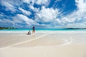 Beautiful tropical beach at Exuma Bahamas with father and son having fun