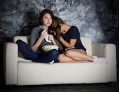Two young girls looks TV at dark room