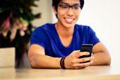 Closeup portrait of a man using smartphone. Focus on smartphone