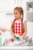 Sulking little girl doing the dishes on parents order