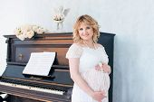 Pregnant Woman Near The Piano. Music For The Baby.