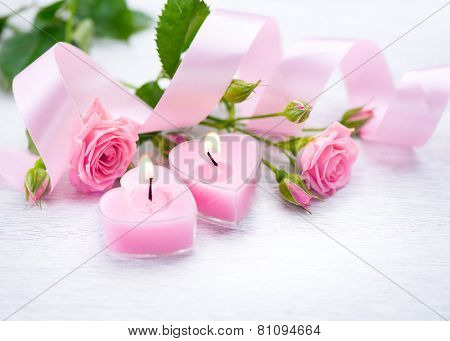 Valentine\'s Day. Valentine Gift. Pink Heart shaped candles and rose flowers on white wooden backgrou