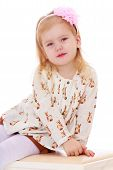 foto of banquette  - Adorable little girl sitting on the banquette - JPG