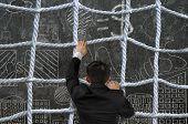 Businessman Climbing Crisscross Rope Net On Business Concept Doodles Background