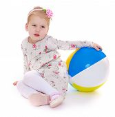 Little girl sitting on the floor and play ball.