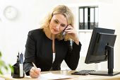 Businesswoman working in office. Employee talking by phone and writing by pen