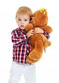 Little boy hugging a teddy bear.