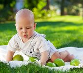 Baby Boy With Green Apples On Green Grass In Summer Park.
