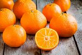 Ripe Mandarins Cut On A Wooden Background