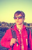 Stylized colorized vintage portrait of young boy hiker holding backpack and looking at the sunset