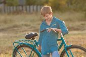 Portrait Of Teenager With Retro Bike In Farm Field