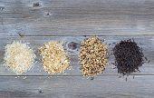 Varieties Of Rice In Piles On Top Of Rustic Wood