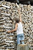 Teenager Arranges Firewood Into Stack Background