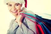Beautiful young woman in santa hat with shopping bags.