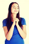 Young hopeful beautiful woman is praying.