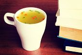 Hot vegetable soup in a cup on table next to books.