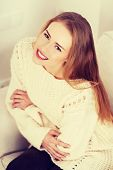 Beautiful woman in bright sweater sitting on a couch and smiling.