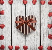 Heart shaped Valentines Day gift box that surrounded by small red hearts on white wood table.