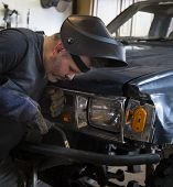 picture of welding  - Man wearing welding helmet holding welding tool in front of truck - JPG