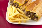 foto of cheesesteak  - A messy Philly Cheesesteak with onions peppers and mushrooms fries on the side - JPG