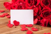 Bouquet of roses with blank paper on wooden desk