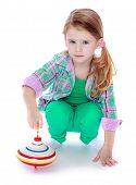 Little girl spinning dreidel.