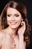 Beauty smiling model with perfect makeup and luxury accessories.