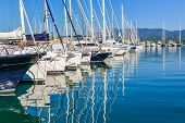 image of sloop  - Panorama of a big Gouvia harbour with white yachts and boats on a beautiful sunny day over the island of Corfu - JPG