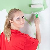 Woman In Red T-shirt With Paint Roller In Hand
