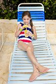 Child enjoying a tropical drink at an outdoor pool
