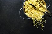 spaghetti in colander on dark vintage background