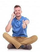 casual young man sitting on the floor with his legs crossed and talking on the phone while showing the thumb up gesture and smiling for the camera. isolated on white