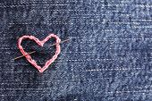 Jeans fabric with pink heart embroidered on it, close-up